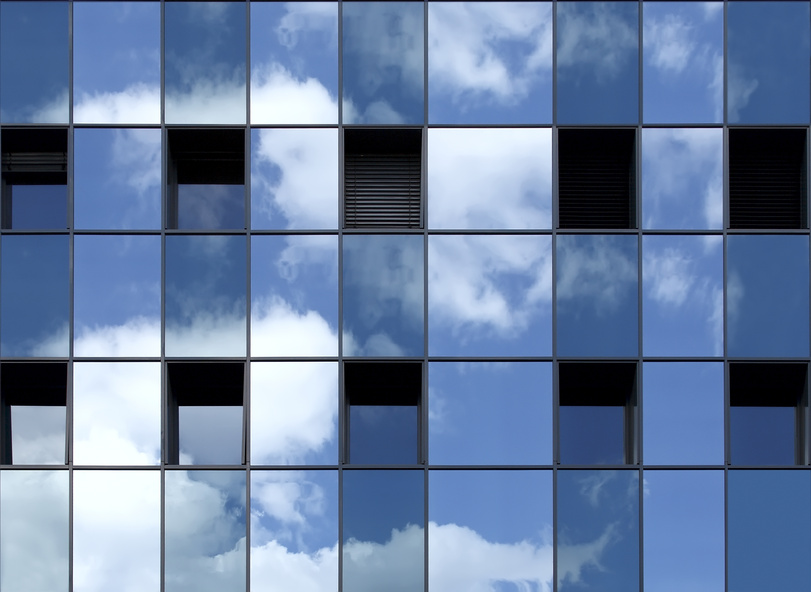 Spiegelung des Himmels in einer blauen Fensterfassade.