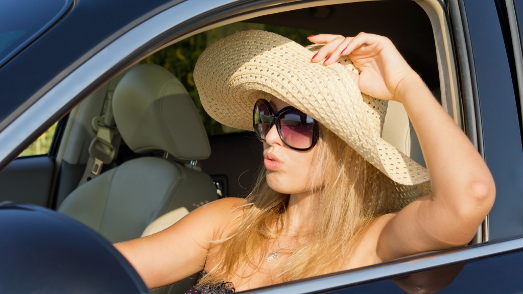 Beautiful woman driver in straw hat sitting in the hot sun with the car window rolled down