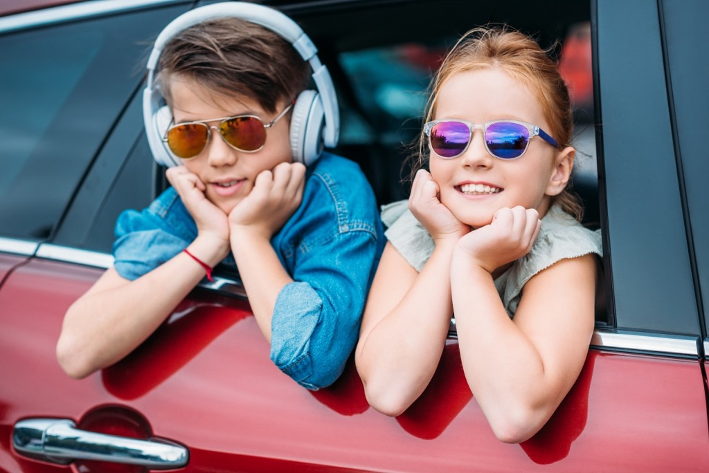 happy kids in sunglasses on car trip looking out of window